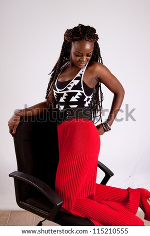 Lovely black woman kneeling backwards in a chair and resting her arm on the back of the chair while she plays with her red slacks - stock photo