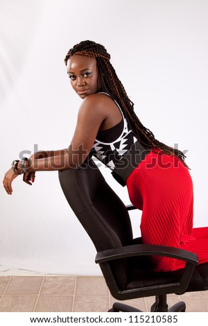 Lovely black woman kneeling backwards in a chair and resting her arms on the back of the chair while she looks at the camera with a playful expression - stock photo