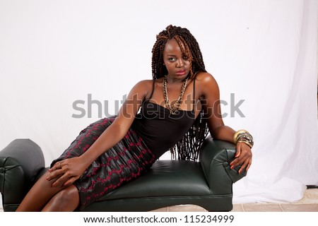 Lovely black woman reclining on a bench with a serious, sexy look for the camera - stock photo