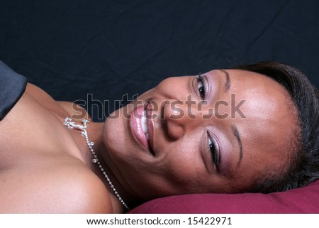 Lovely black woman smiling at the camera - stock photo