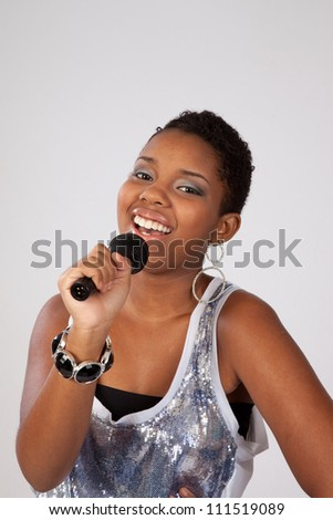 Lovely black woman with a microphone, and singing with joy and pleasure