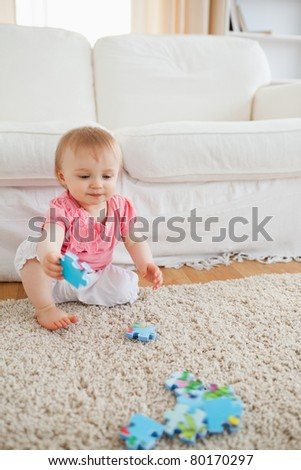 Lovely blond baby playing with puzzle pieces while sitting on a carpet in the living room - stock photo