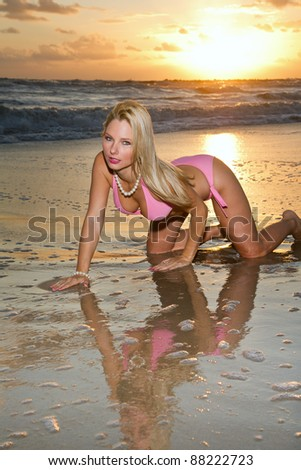 lovely blond female in bikini on florida beach with windy morning surf, with fill flash - stock photo