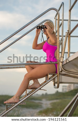 lovely blond female in one-piece swimsuit scans beach with binoculars - stock photo