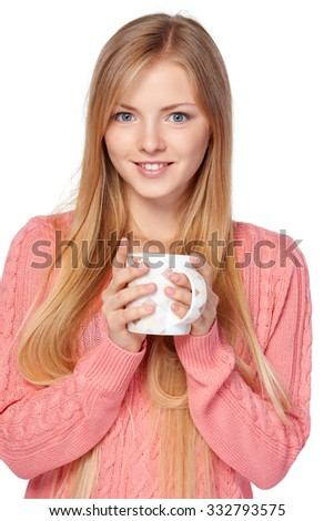 Lovely blond female in pink knit sweater standing casually holding a hot drink in a cup over white studio background - stock photo