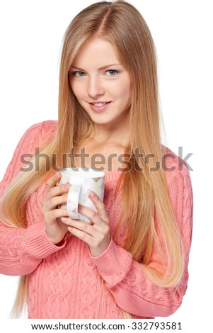 Lovely blond female in pink knit sweater standing casually holding a hot drink in a cup over white studio background