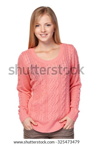 Lovely blond female in pink knit sweater standing casually with hands in pockets over white studio background - stock photo