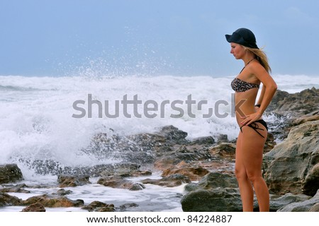 lovely blond female on beach as hurricane irene brushes florida coast with rain and wind in august 2011 - stock photo