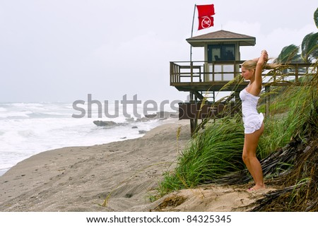 lovely blond female on beach as hurricane irene brushes with rain and wind in august 2011 - stock photo