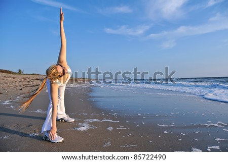 lovely blond female stretching at pristine florida beach in morning - stock photo