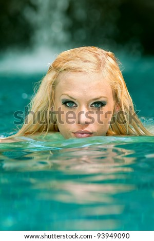 lovely blond female swimmer coming up for air in tropical pool
