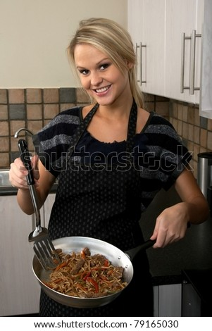 Lovely blond housewife preparing a delicious stir fry meal - stock photo