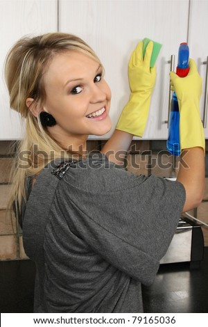Lovely blond housewife wearing yellow gloves and cleaning the kitchen - stock photo