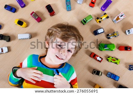 Lovely blond kid boy playing with lots of toy cars indoor. Child boy wearing colorful shirt and having fun. - stock photo
