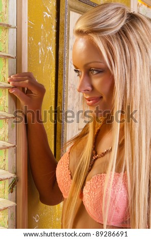 lovely blond lingerie model looking out a window