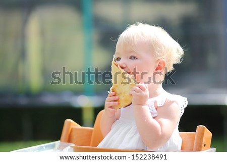 Lovely blond little baby girl in beautiful white dress biting on piece of tasty pizza holding it with two hands - stock photo