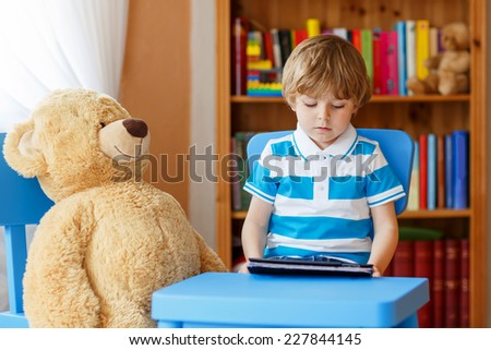 Lovely blond preschool kid boy playing with tablet computer in his room at home, indoors. - stock photo