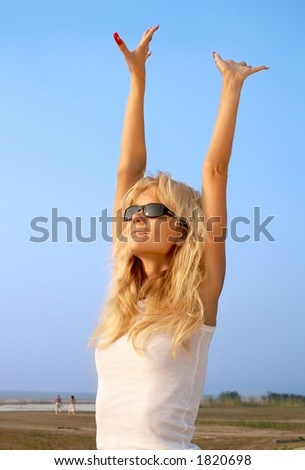 lovely blond raising hands to the sun - stock photo