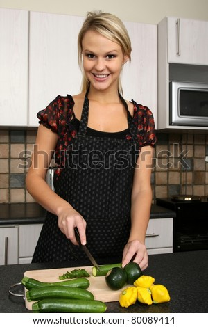 Lovely blond woman cutting vegetables on a chopping board - stock photo