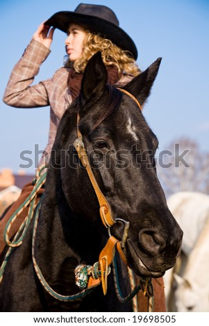 Lovely blond woman in a hat riding in countryside - stock photo