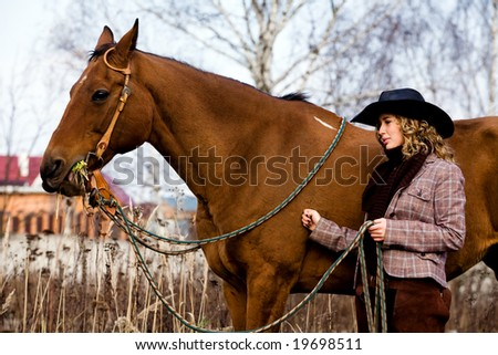 Lovely blond woman in a hat standing by horse outdoors