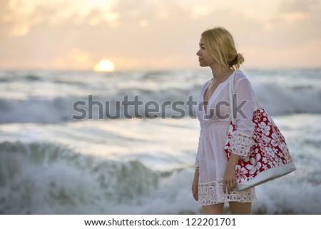 lovely blonde female walking along beach at dramatic sunrise - stock photo