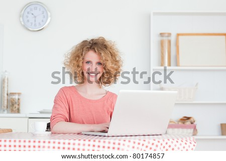 Lovely blonde woman relaxing with her laptop while sitting in the kitchen in her apartment - stock photo