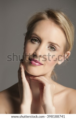 Lovely blonde woman wearing natural makeup and touching her face with her hands - stock photo