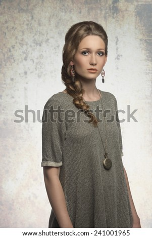lovely blonde woman with braid hair-style posing in fashion shoot with gray dress and stylish necklace  - stock photo