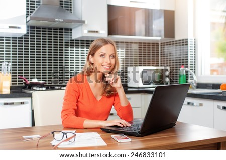 Lovely blonde woman working with her laptop while sitting in the kitchen in her apartment holding her chin and looking at camera - stock photo