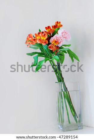 Lovely bouquet of flowers arranged in a glass vase against a neutral wall.