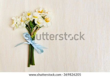 lovely bouquet of narcissus with a charming blue bow on beige cotton - stock photo