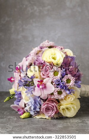 Lovely bouquet of pink orchids, chrysanthemums and hortensias mixed with yellow roses and violet eustomas.