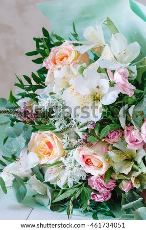 Lovely bouquet with different kind of flowers on a wooden background
