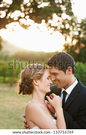 Lovely bride and groom holding hands while facing each other and smiling as the sun sets in the background - stock photo