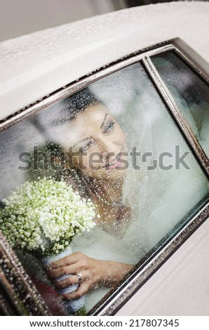 Lovely bride in old car at wedding in rainy day - stock photo