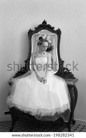 Lovely bride sitting on a hotel commode and having a large flowers bun. A black and white image with grain added as effect. - stock photo