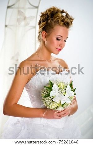 Lovely bride with bouquet of flowers close-up portrait - stock photo