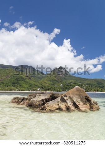 Lovely bright vertical sea landscape with big stones of volcanic origin, with mountains covered with tropical plants and clean clear waters of the Indian Ocean, Seychelles - stock photo