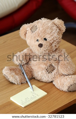 Lovely brown teddy bear adding honey to the shopping list - stock photo