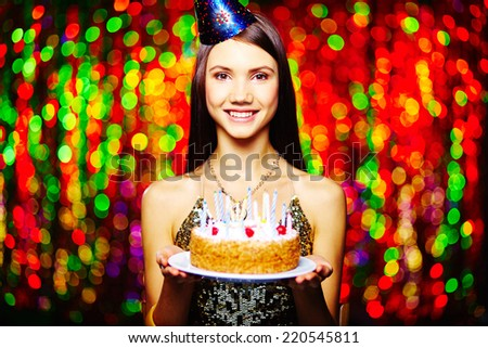 Lovely brunette with birthday cake looking at camera on sparkling background