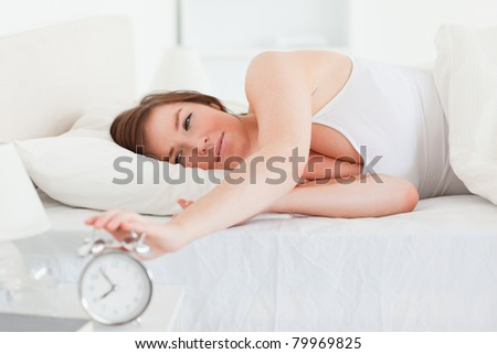 Lovely brunette woman turning off a clock while lying on a bed - stock photo