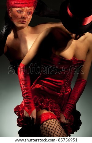 Lovely cabaret performers on stage isolated on dark background - stock photo