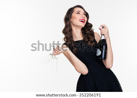 Lovely carefree joyful young woman with retro hairstyle laughing and holding bottle of champagne and two glasses - stock photo