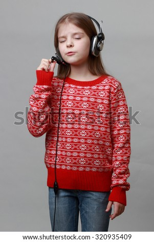 Lovely caucasian little girl wearing red christmas sweater is singing - stock photo