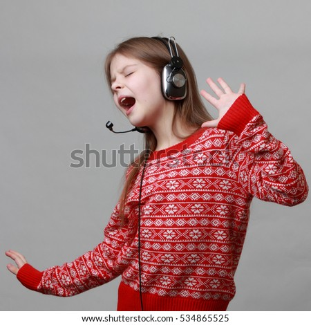 Lovely caucasian little girl wearing red christmas sweater is singing