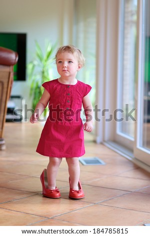 Lovely child, cute funny little toddler girl in beautiful dress trying mom's red high heel shoes walking at home along the living room with tiles floor and big windows - stock photo