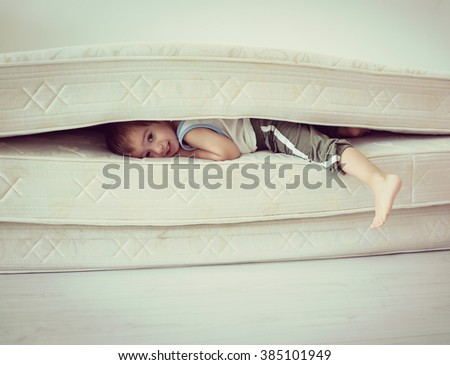 Lovely child laying down on the bed - stock photo