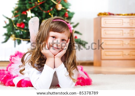 Lovely child lying, Christmas tree in the background