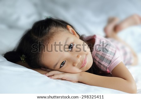 Lovely child lying on light blue blanket - shallow depth of field focusing on her eyes looking at the camera - stock photo